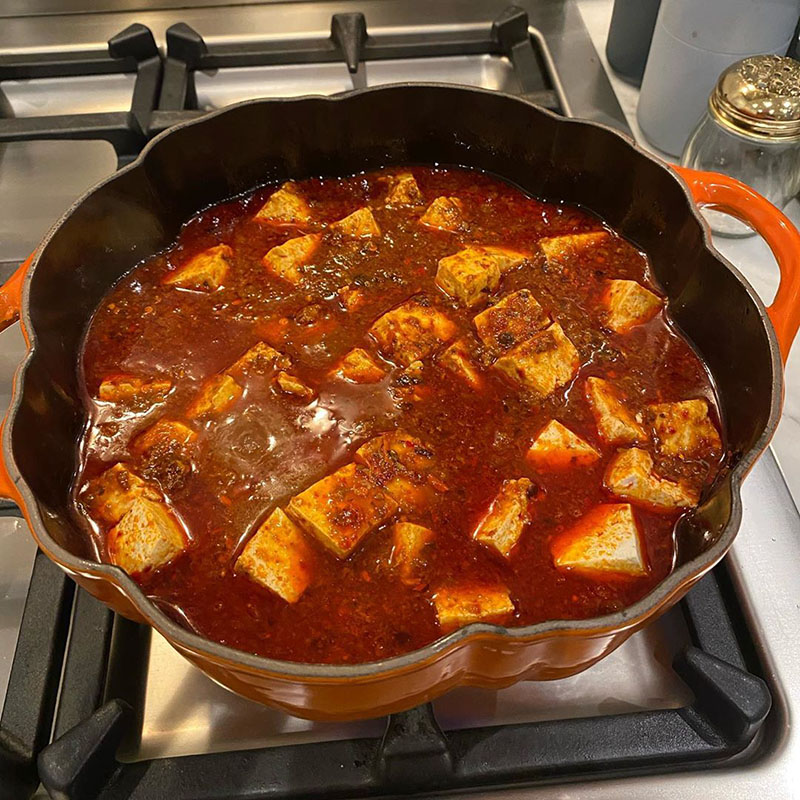 Photo of mapo tofu in progress: tofu has been nestled into the broth.