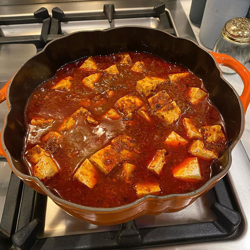 Photo of mapo tofu in progress: tofu has been nestled into the broth.