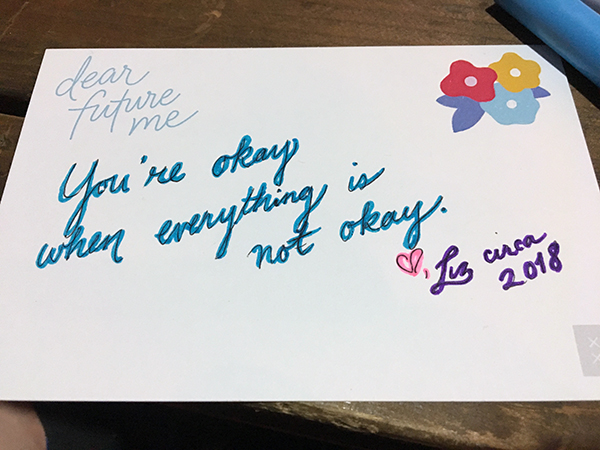 A postcard with scripted writing: Dear future me, You're okay when everything is not okay. ♡, Liz circa 2018